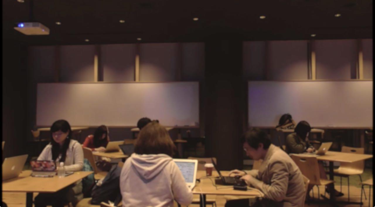 WCAGもくもく会の会場の写真。薄暗い部屋で数人がPCに向かってもくもくしている様子が映っている。