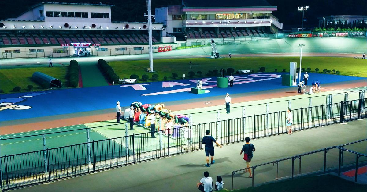 写真: 夜の競輪場。発走前にスタートポジションにつく選手をライトが照らし、数人の観客が見守っている