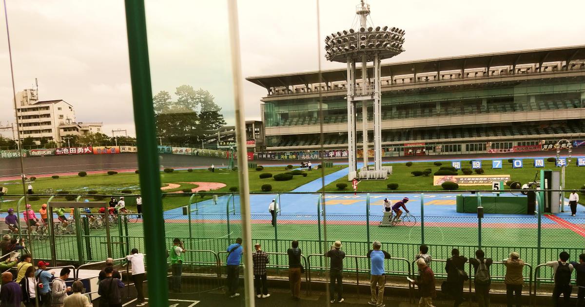 写真: 昼の競輪場。発送前、先頭誘導員が準備を終え、選手たちが発送前のルーチンをおこなっているところをそこそこの観客が見ている