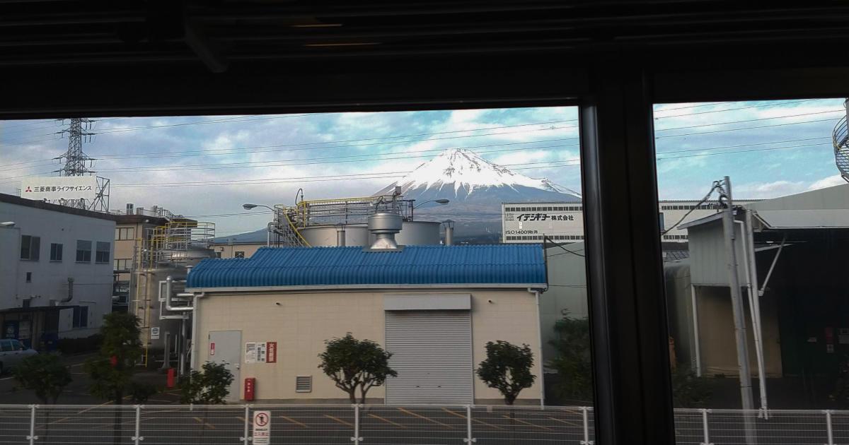 車窓から見た富士山。建物の置くに雪をかぶった富士山が見える