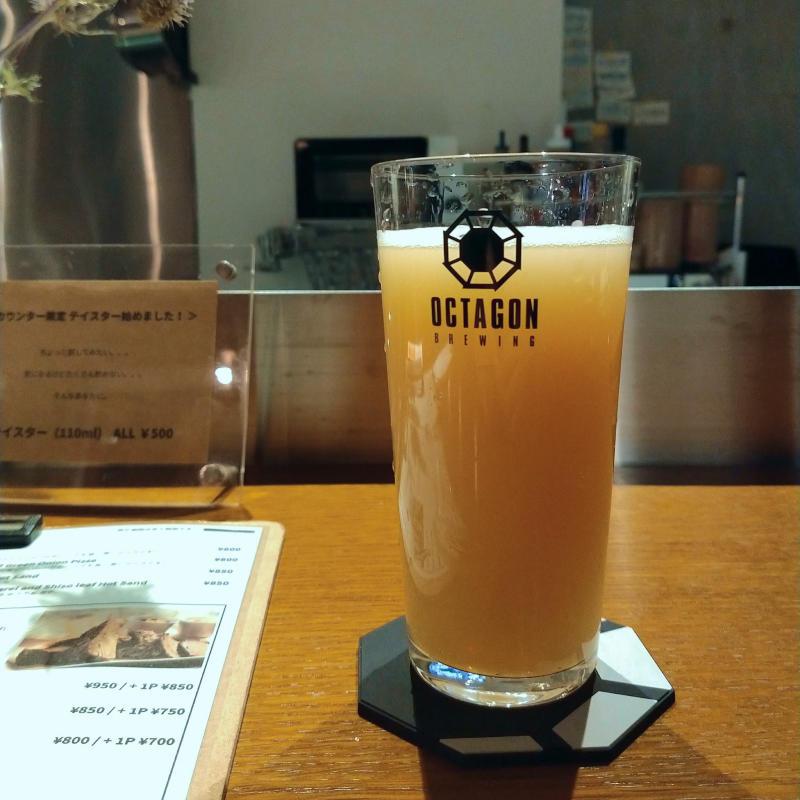カウンターに置かれたビール。白く濁った桃色のビール。