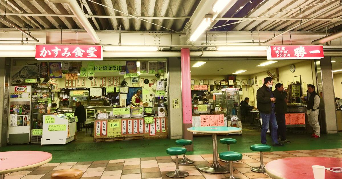 場内の写真、「かすみ食堂」と「どて煮、焼きそば、トンテキ 勝一」の2店。黄色の紙にかかれたメニューがいたるところに貼ってある。